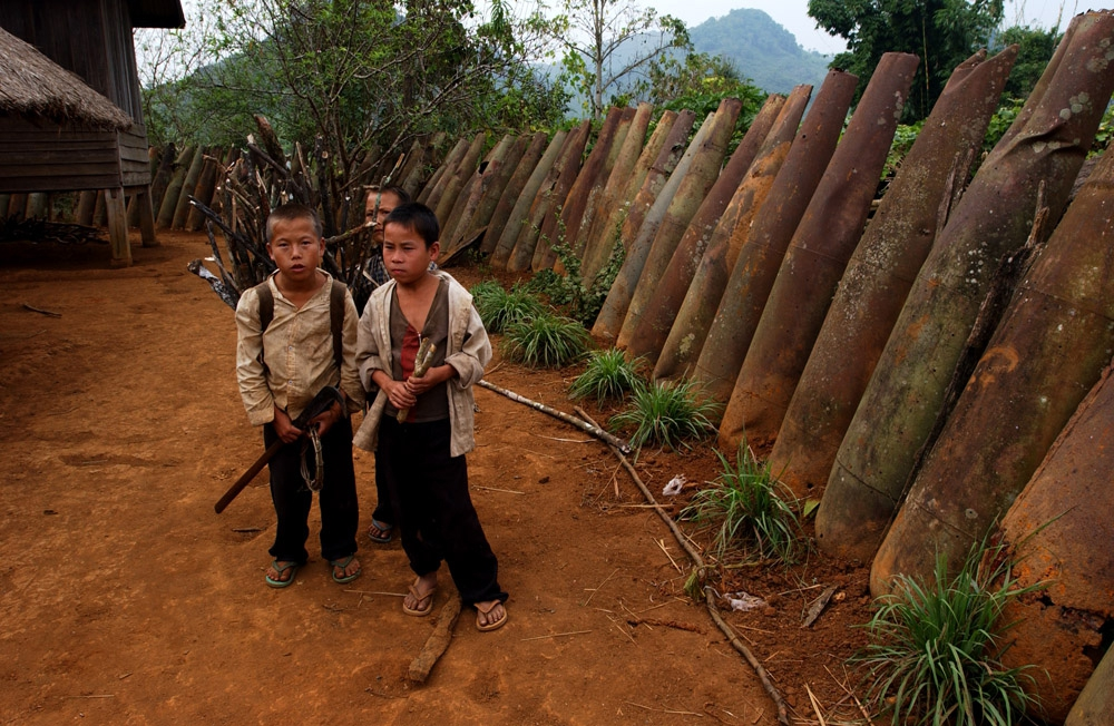 Laos: children play next to a wall of unexploded bombs